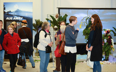 Attendees view installation in the museum featuring poster, video and decorative elements.