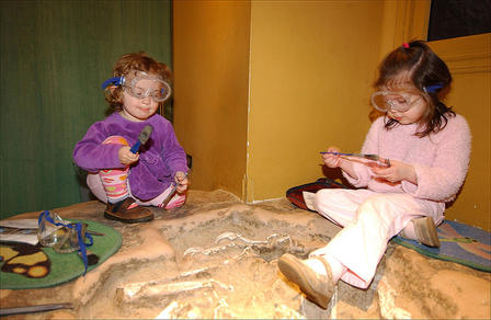 "Two children with googles and tools perch on a sand pit that holds ""fossils"" waiting to be discovered."