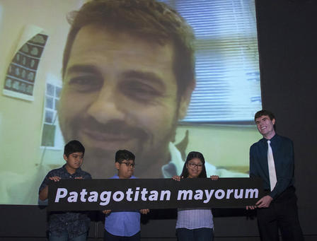Four people hold a sign reading Patagotitan mayorum while Diego Pol smiles on a Skype call displayed on a large screen behind them.