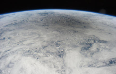 Partial view of the earth as seen from space with a large shadow on cloud cover.