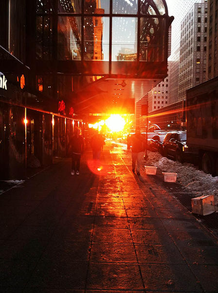 Sun shines at street level between tall office buildings.