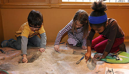 Three children dig in an indoor sand pit in the Museum's Discovery Room.