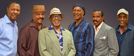 Six members of the Persuasions stand side-by-side in a smiling group portrait.