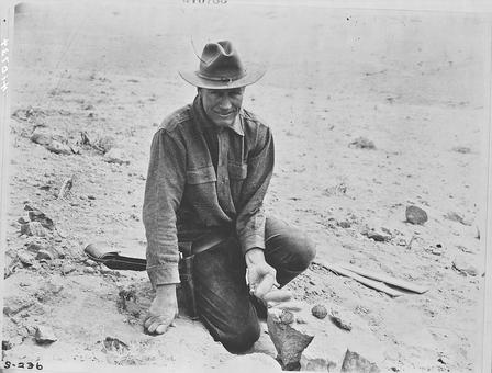 Roy Chapman Andrews smiles for the camera as he sits in the Gobi desert holding a rock embedded with multiple fossilized dinosaur eggs.