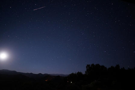 A nighttime landscape shows the glow of the moon and a meteor streaking through the night sky.