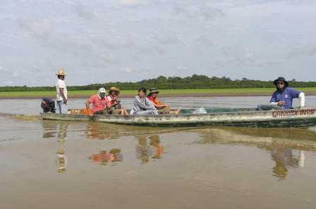 Five people are seated in a low long boat, and one person stands at the motor guiding the boat along the river.