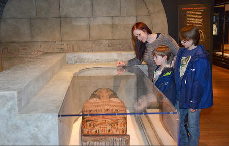 Adult and two children view a mummy sarcophagus in a display that recreates the stone interior of an egyptian tomb.