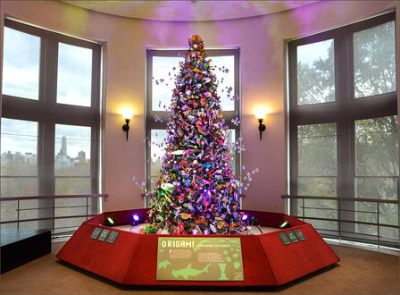 Tall, artificial evergreen tree, covered in origami decorations, stands on pedestal in a bay window.