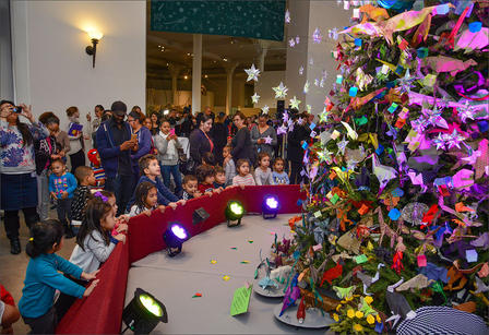 Children gather around the base of an artificial evergreen tree that is covered with origami decorations.