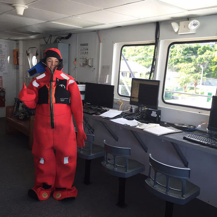 Paasch stands inside a research vehicle wearing a puffy, full-body suit.