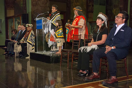 Person in ceremonial dress stands at podium and speaks while several other people  in ceremonial and regular dress sit on either side.