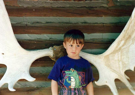 Young Zac stands in the middle of a massive pair of antlers that are mounted on a log cabin wall.
