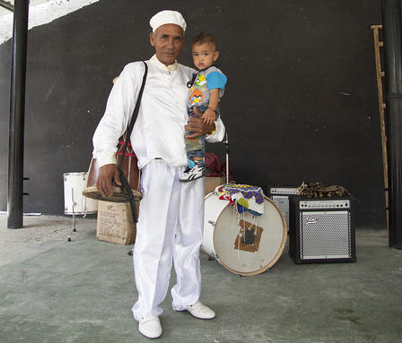 Francisco stands in front of bass drum and other musical equipment. He wears a white cap, shirt, pants and shoes, holds a toddler-aged child.