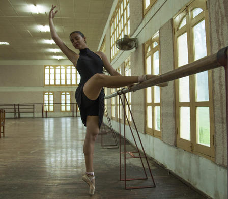 Katherine practices ballet, and stands on one leg en pointe, her other leg resting on the barre and one arm raised.