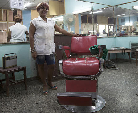 Mirta stands next to an old-fashioned style leather barber chair, with the mirrors of the salon in view behind her.