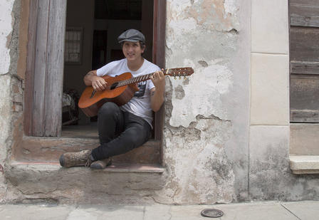 Pablo sits outside on the steps leading to the entrance of his building and plays an acoustic guitar.