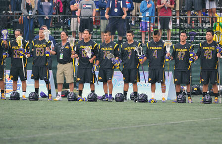 Group of players stand side-by-side, holding their lacrosse sticks.