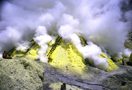 Steam rises from large pile of sulfur.
