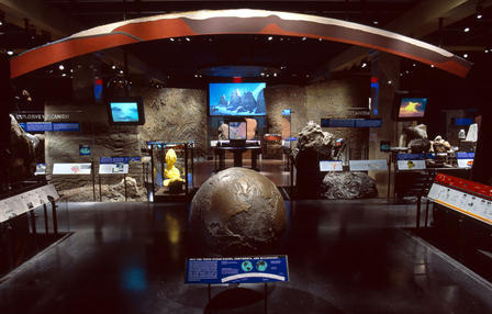 Large bronze model of planet earth is displayed in the middle of a Museum hall which contains geological specimens.