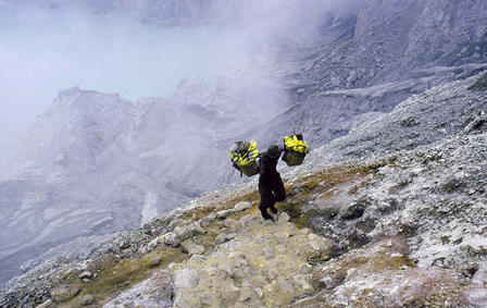 Miner carries baskets of sulfur across his shoulders as he walks up the mountain.