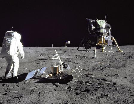 Το Buzz Aldrin φοράει ένα ογκώδες κοστούμι και κράνος και στέκεται στην επιφάνεια του φεγγαριού δίπλα σε ένα επιστημονικό όργανο.