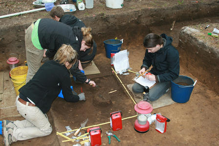 Four people at work in an excavation pit, using tools and recording information.