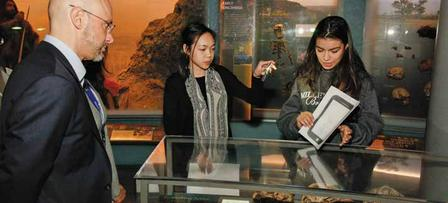 High school students Monica Chhay and Sarah Carrillo show a visitor how to use a smartphone to create virtual Neanderthal tools. © AMNH/M. Shanley