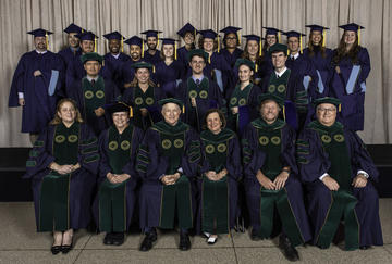 Graduates, faculty, Museum administrators, and the honoree in academic regalia pose for a photo.