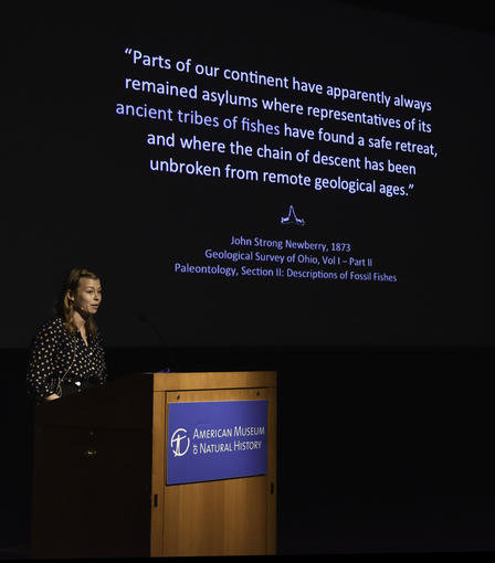 Allison Bronson speaks from a podium, text is visible on the screen behind her and describes the evolution of fossil fishes.