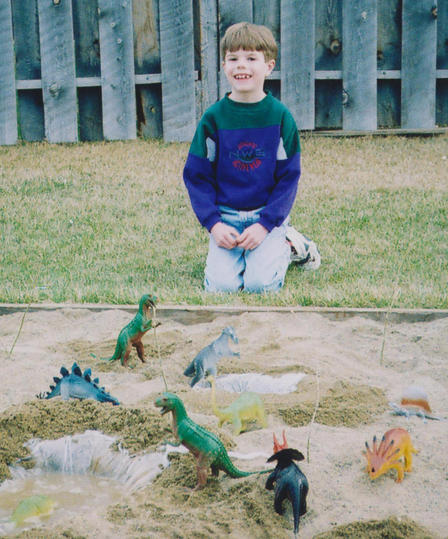 Childhood photo of Danny Barta kneeling next to a sand pit where has posed an assortment of plastic dinosaurs.