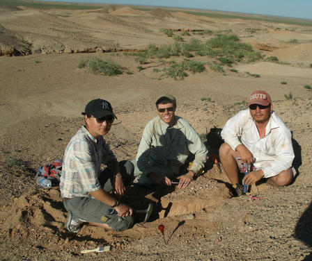 Danny Barta and two colleagues sit on the sand near an excavation site in the Gobi desert.