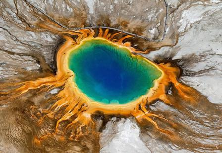 The astounding colors of Yellowstone National Park's Grand Prismatic Spring are produced by bacteria that live in the hot spring's waters.  © NPS/J. Peaco
