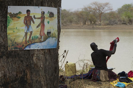 A woman does her washing near a dam in the country now known as South Sudan. Nearby, a sign cautions against entering the water while infected with Guinea worm. © The Carter Center/L. Gubb