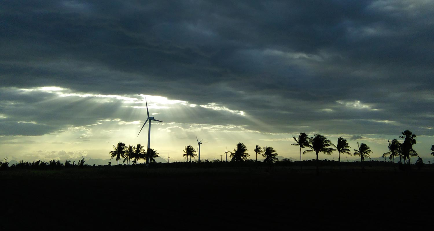 Cloudy sky with sun going trough and silhouettes of windmills and palm trees