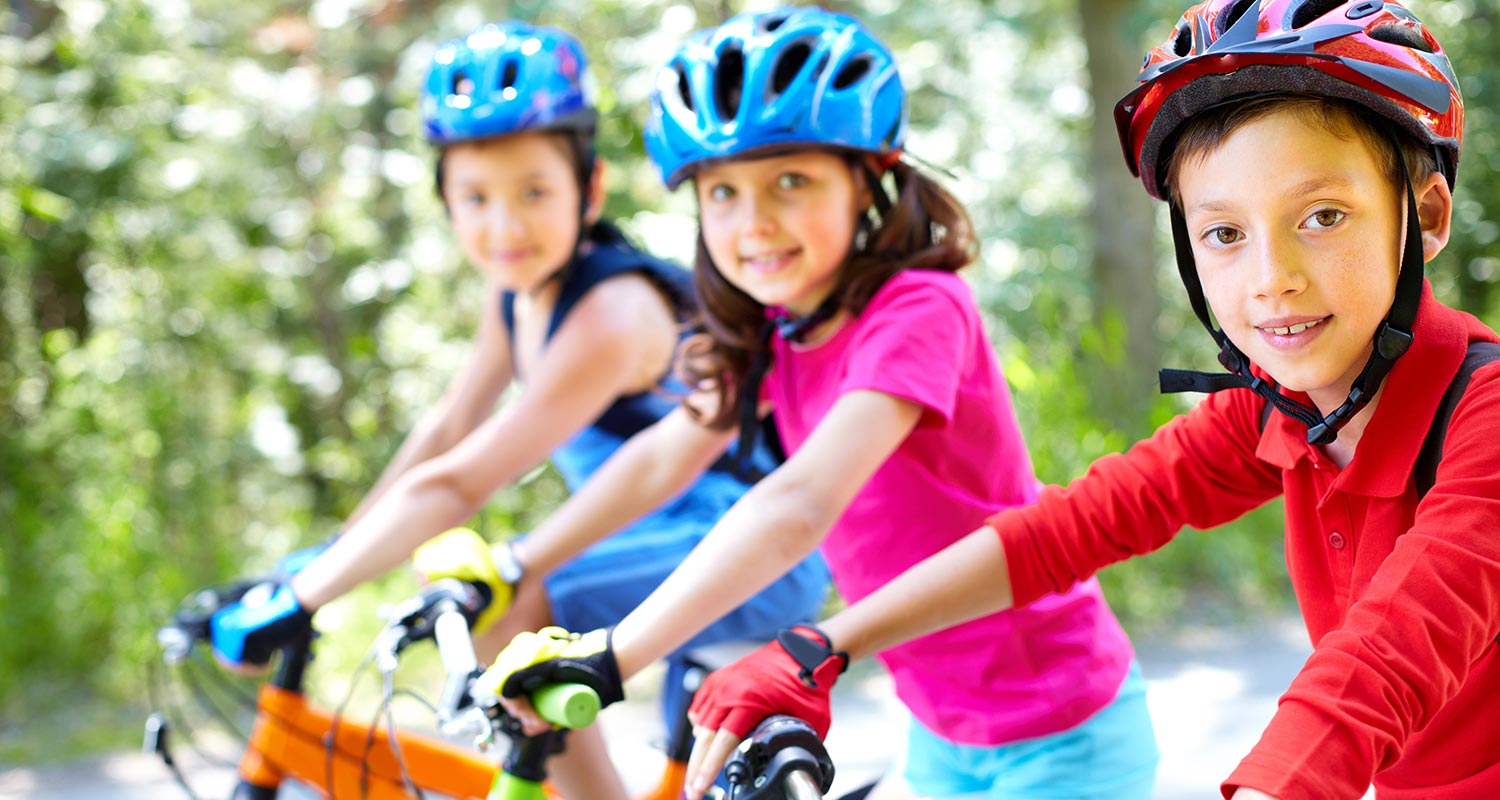 Three kids on their bikes wearing helmets