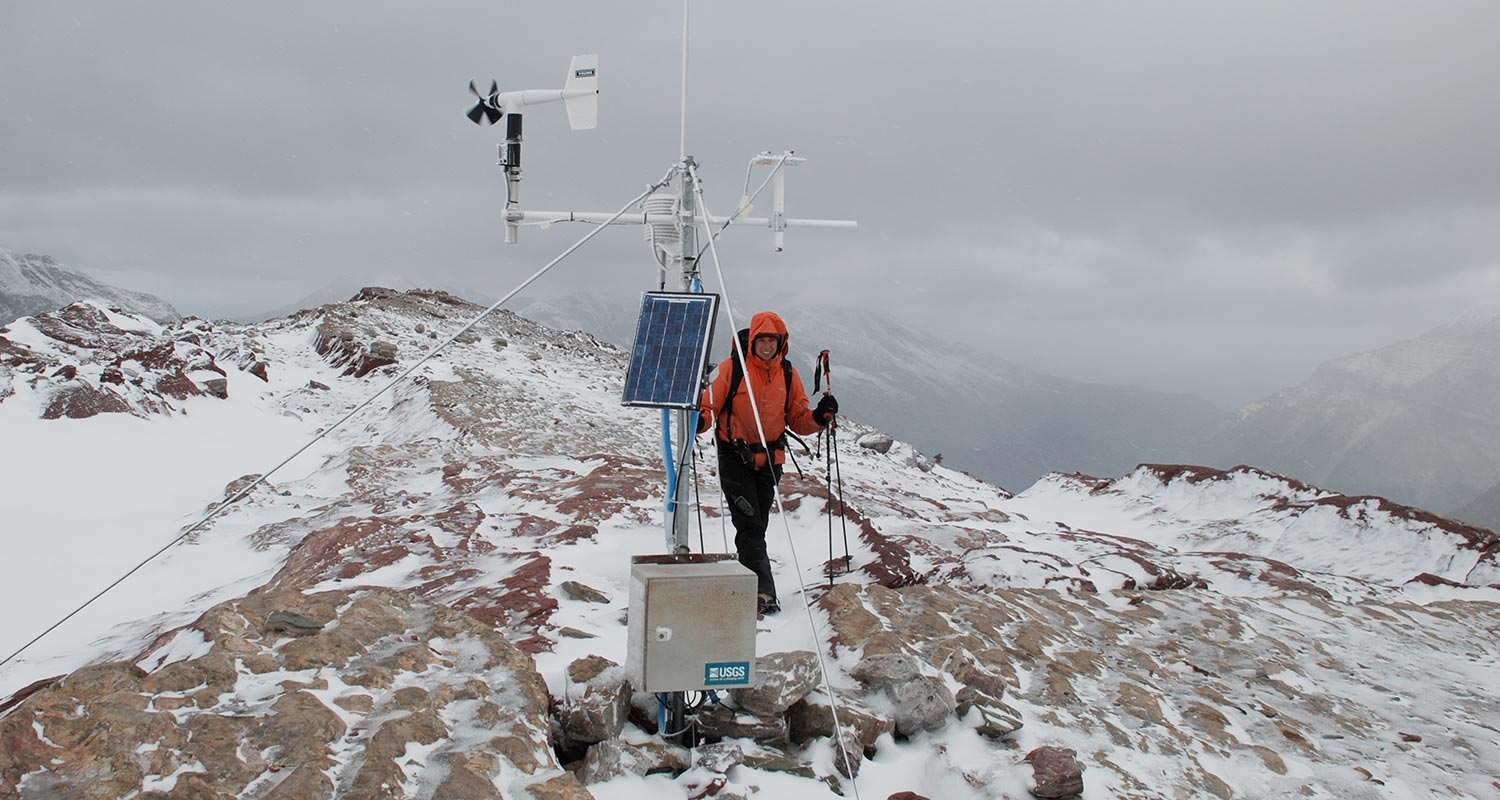 Scientist collecting data from weather station located at snowy mountain