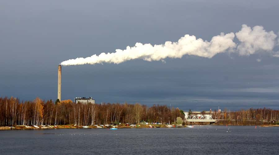 power plant near river's edge with billowing smoke stack