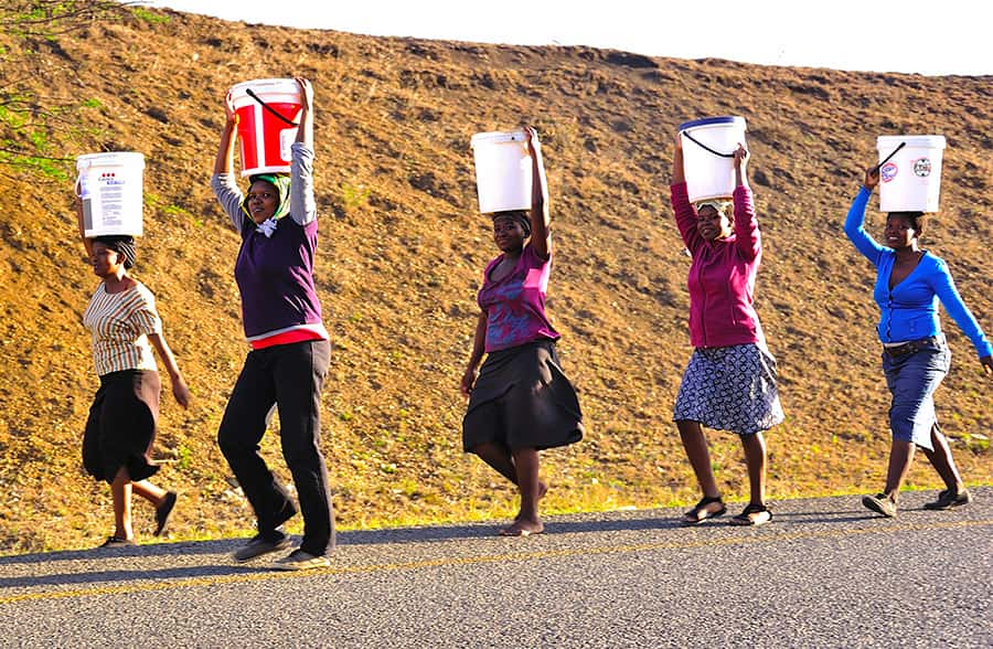 zulu women carrying water buckets on their heads