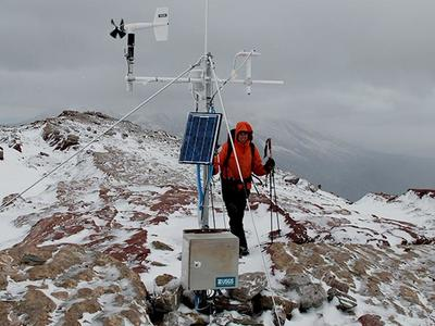 Scientist at weather station on top of a snowy mountain