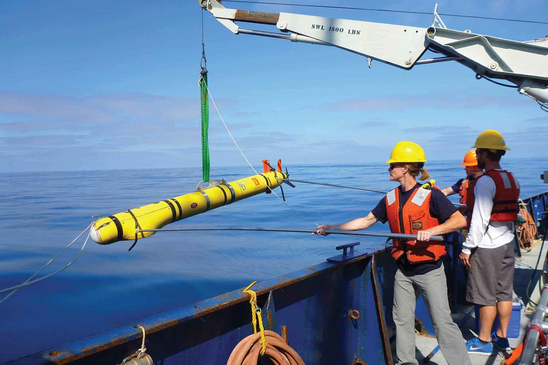 Scientists, aided by a small crane, prepare to deploy a torpedo-shaped REMUS vehicle into the the ocean.