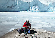 Mountaineer Benjamin Vicenio collects primeval plants by a glacial lake at the Quelccaya ice cap. Lonnie Thompson