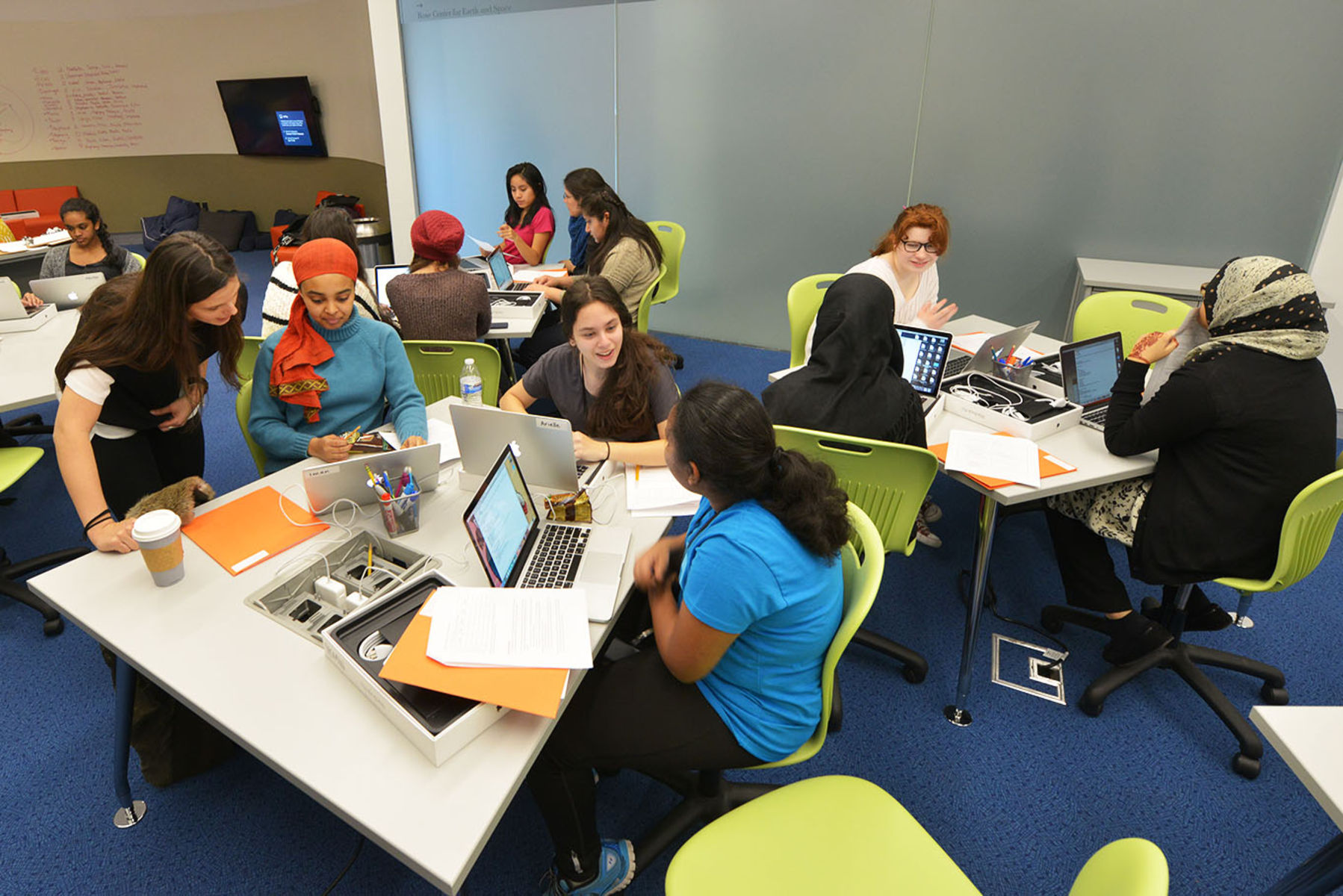 A large group of students gather at several tables with laptops to study and converse.