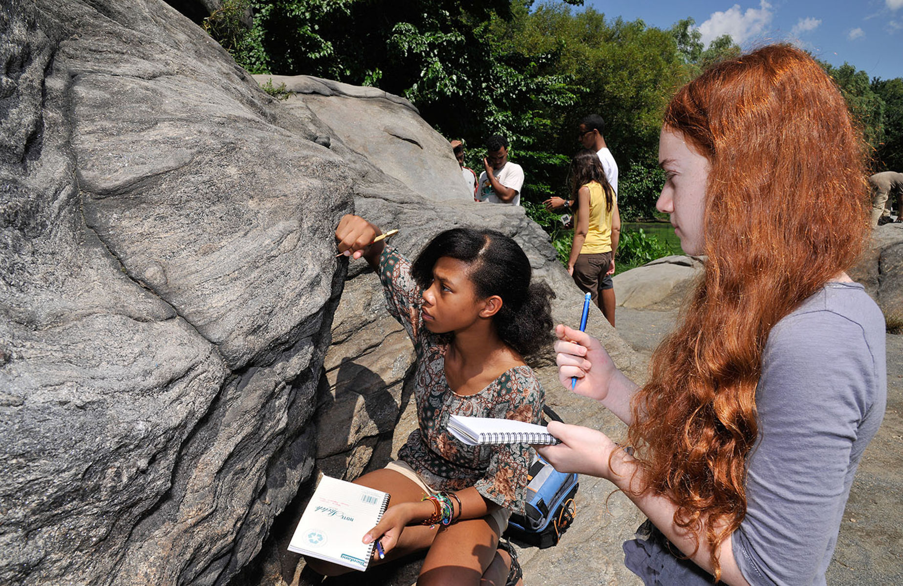 Two students in the field in Central Park peer closely at a large boulder and make notes in notepads.