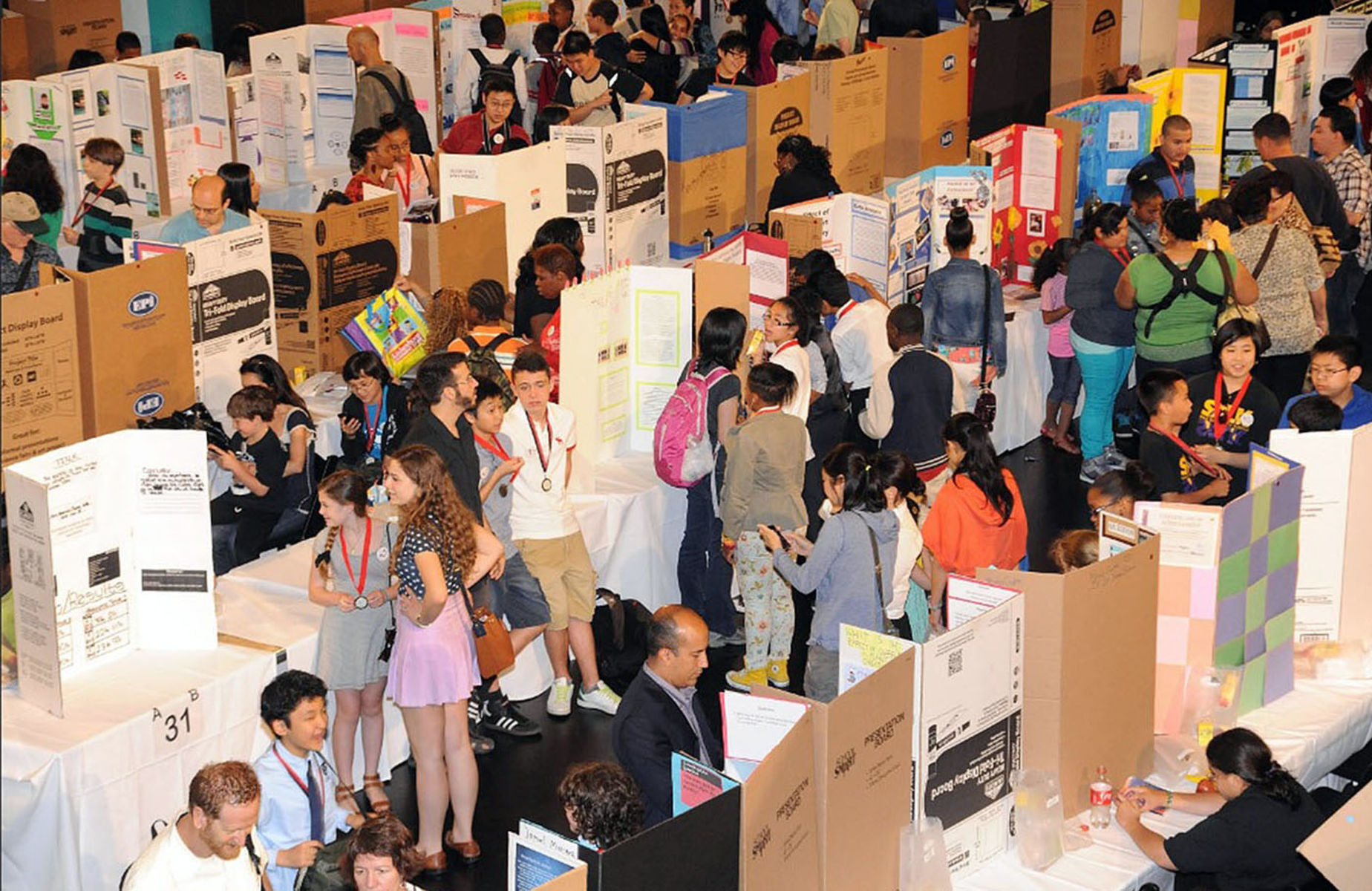Open space with hundreds of students stand in front of cardboard backdrops created to illustrate each student's project.
