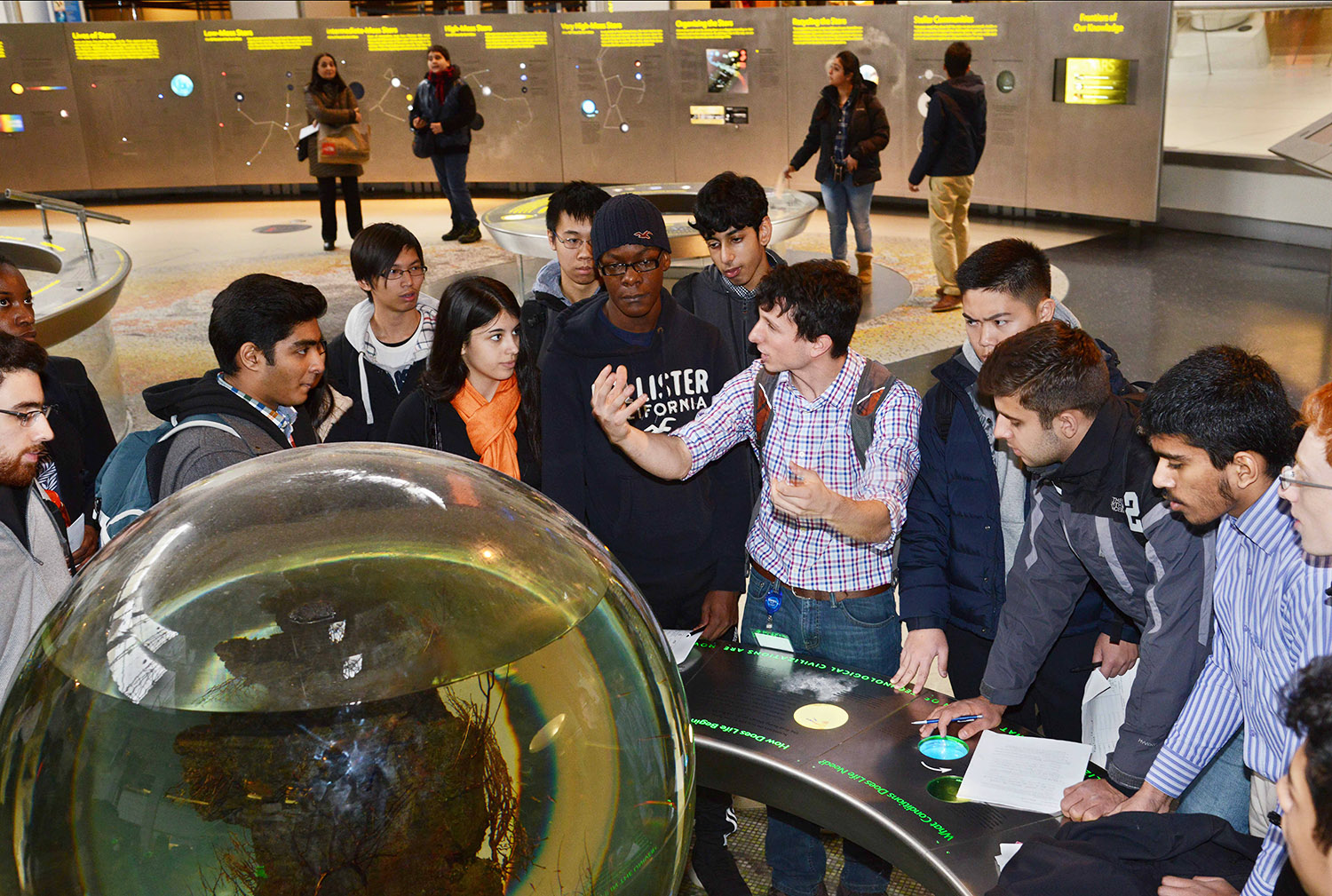 MAT stands in front of an exhibit object in the Rose Center, describing it to surrounding high school students who listen and make notes.