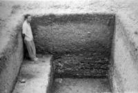 Black-and-white photo of a researcher standing inside an excavated rectangular hole.