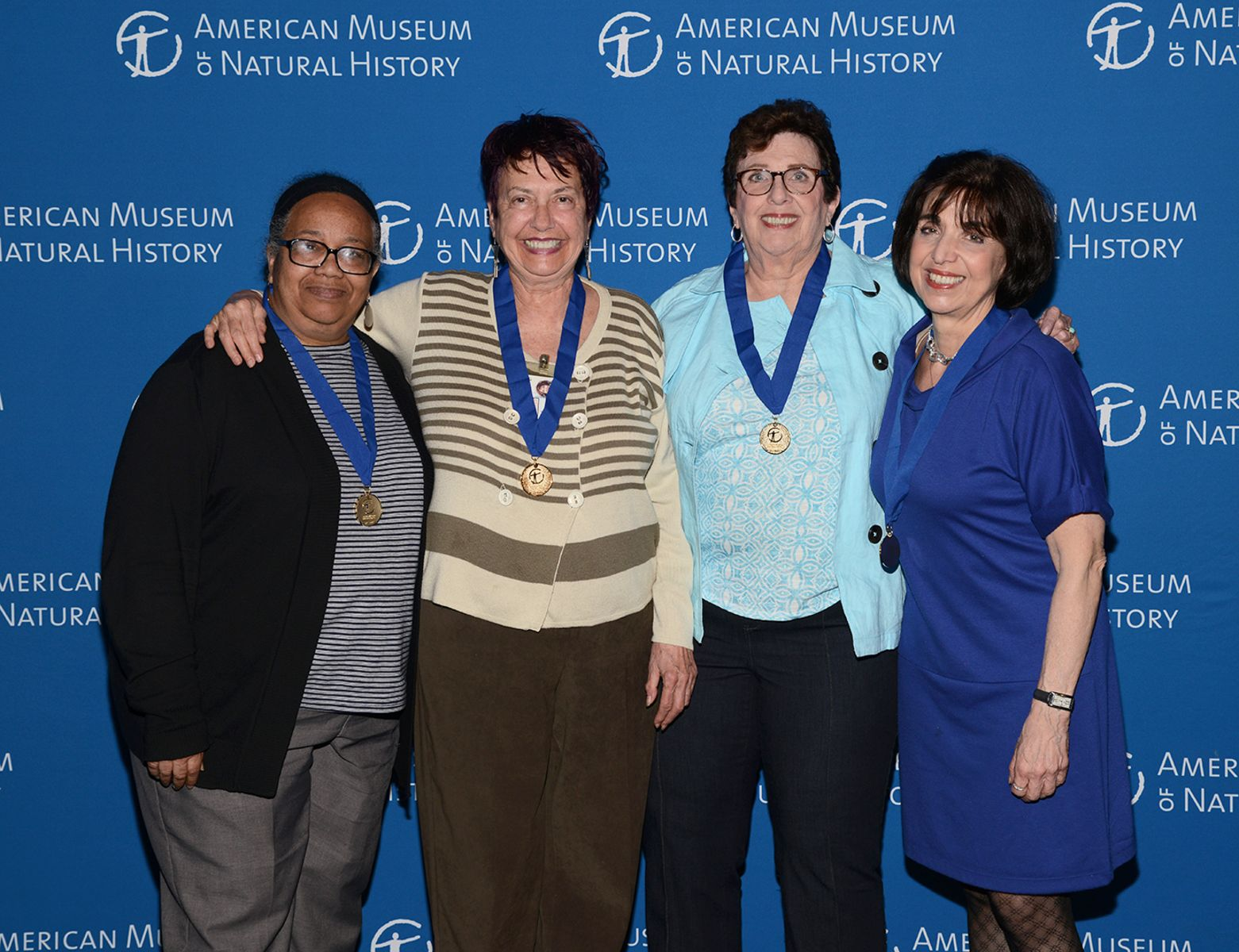 Four smiling women stand with their arms around each other, wearing medals on ribbons around their necks.