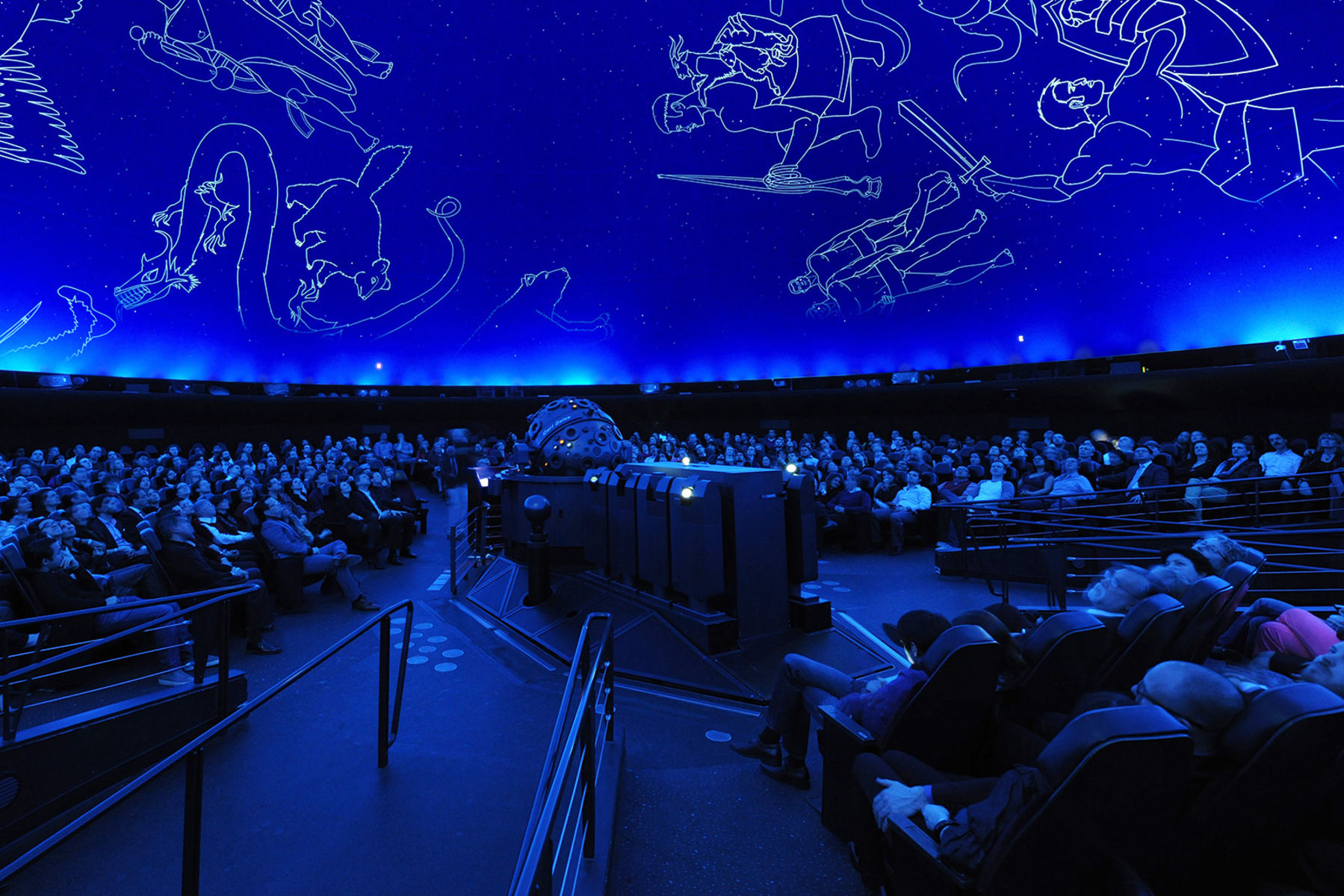 Inside the Hayden Planetarium theater, visitors look upwards at representations of the constellations projected above.