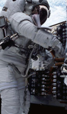 Person wearing a space suit standing and working at an instrument control panel.