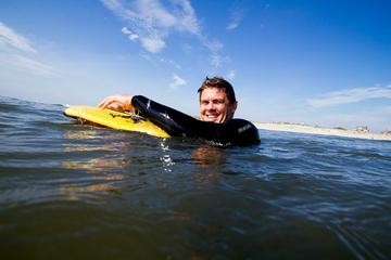 MAT Adjunct Faculty Michael Vericker in ocean water holding surf board near the beach.